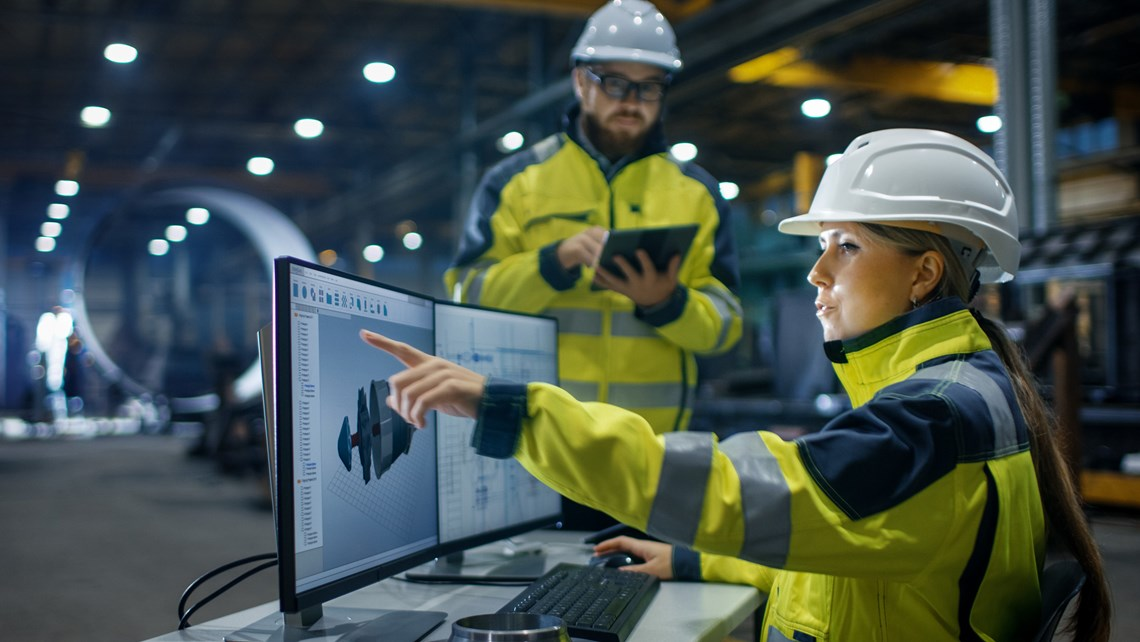 Worker in front of computer screens in an industrial environment